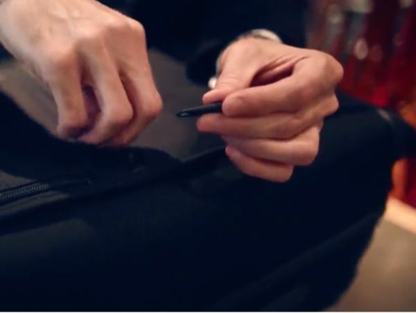 A man repairs a zipper on luggage.