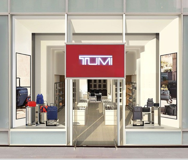 The outside of a Tumi store in a mall showing the logo and products in the window.