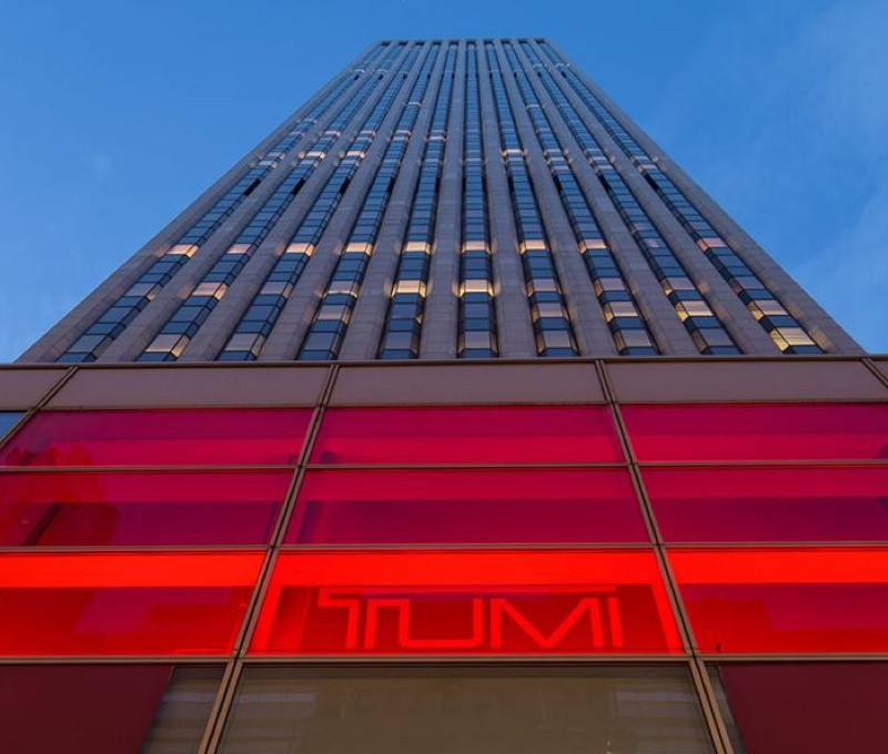 Tumi store building in the evening with red-lit sign.