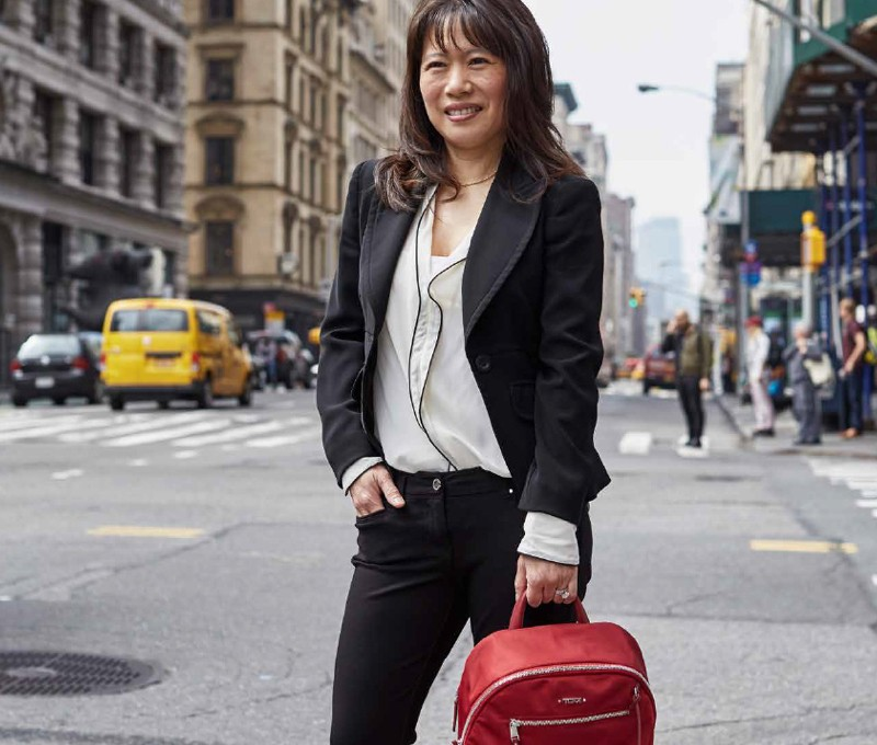 A woman product designer stands smiling in the streets of Manhattan with her Tumi backpack.