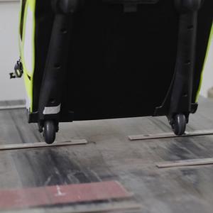 Luggage on rolling test machine testing wheels.