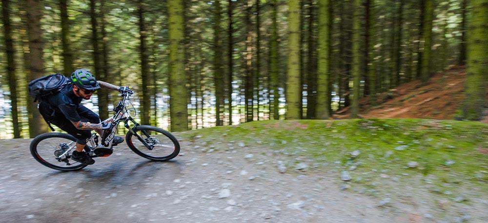 A rider hits a berm on an electric mountain bike