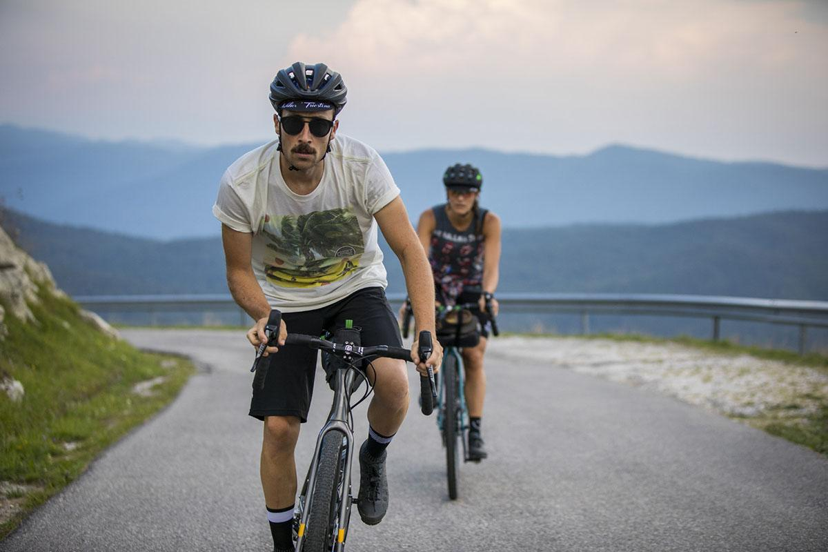 Two bikepackers on road bikes going up a hill