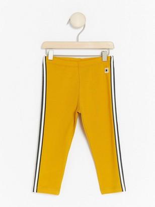 Keltaiset leggingsit, joissa sivuraidat Keltainen