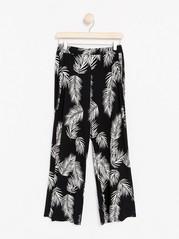 Kuviolliset housut, joissa on leveät lahkeet Musta