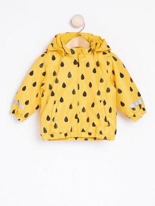 Keltainen takki, jossa mustia sadepisaroita Keltainen