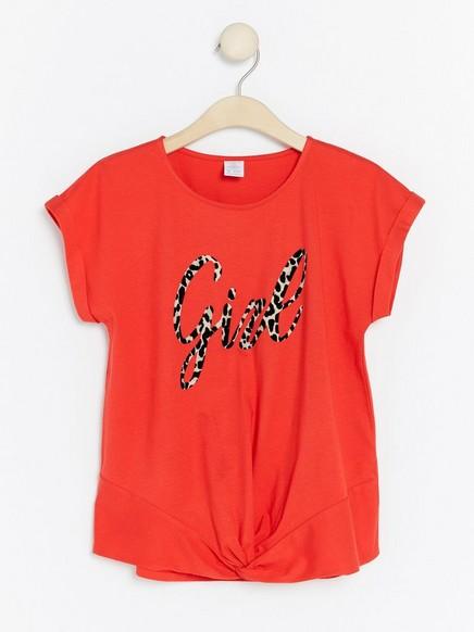 T-paita, jossa solmu ja teksti Punainen