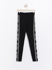 Mustat leggingsit, joissa GRL PWR -sivuraidat Musta
