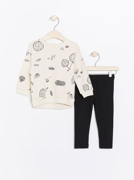 Sett med hvit, mønstret genser og svarte leggings Beige
