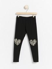Black leggings with leo printed hearts on knees Black