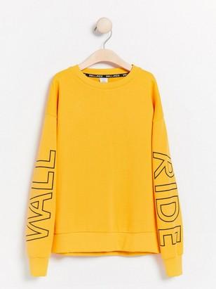 Oversize sweatshirt med tryck på ärmar Gul