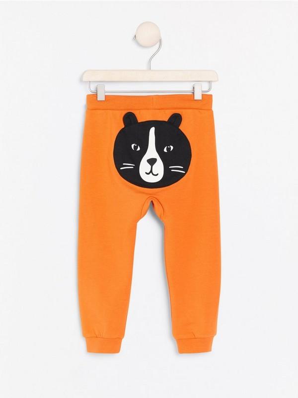 Oranssit trikoohousut, joissa kissa-applikointi takana Oranssi
