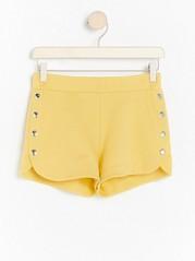 Keltaiset shortsit, joissa napit Keltainen
