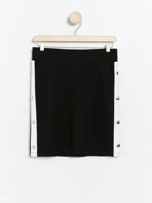 Musta trikoohame, jossa valkoiset sivuraidat Musta