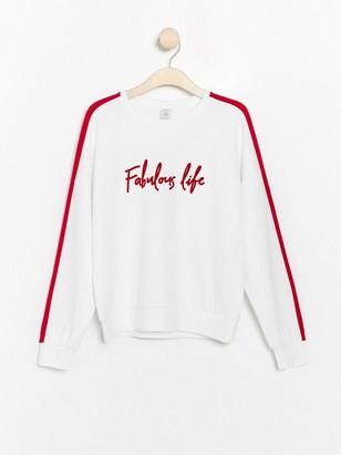 Vit sweatshirt med rött tryck och revär Vit