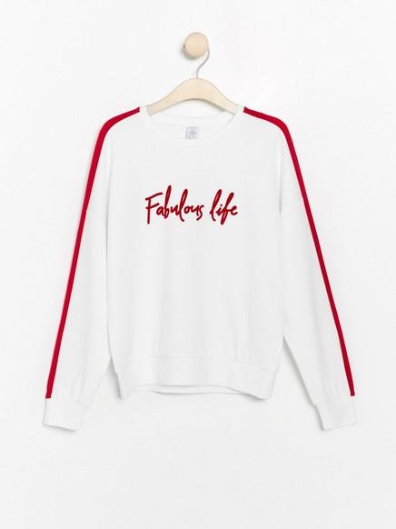 Valkoinen collegepusero, jossa punainen painatus ja raidat sivuilla Valkoinen