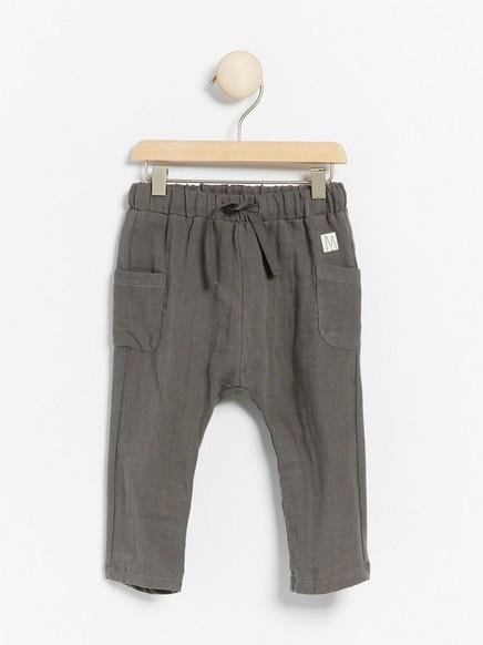 Harmaat housut, joissa kudottua kangasta edessä ja trikoota takana Harmaa