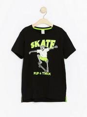 Svart T-skjorte med neonfarget skatetrykk Svart