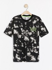 Lyhythihainen t-paita, jossa solmuvärjätyn näköinen kuvio ja neonpainatus Musta