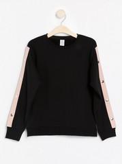 Musta collegepusero, jossa vaaleanpunaiset sivuraidat ja metallinapit Musta