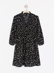 Blommönstrad klänning med smockdetalj Svart